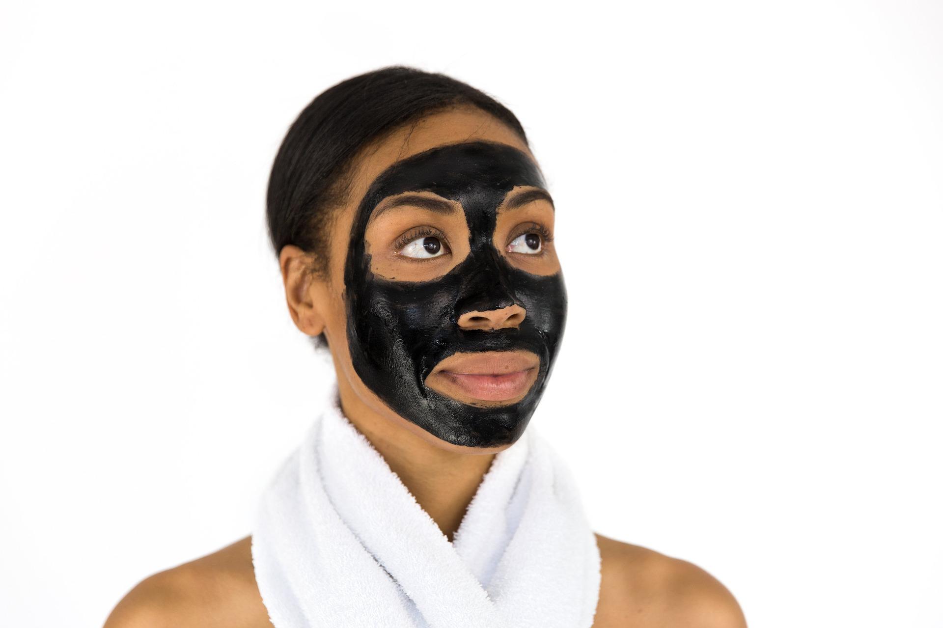 Frau trägt eine schwarze Gesichtsmaske aus Creme.