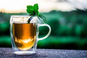 Ein Glas Tee mit einer Minze.