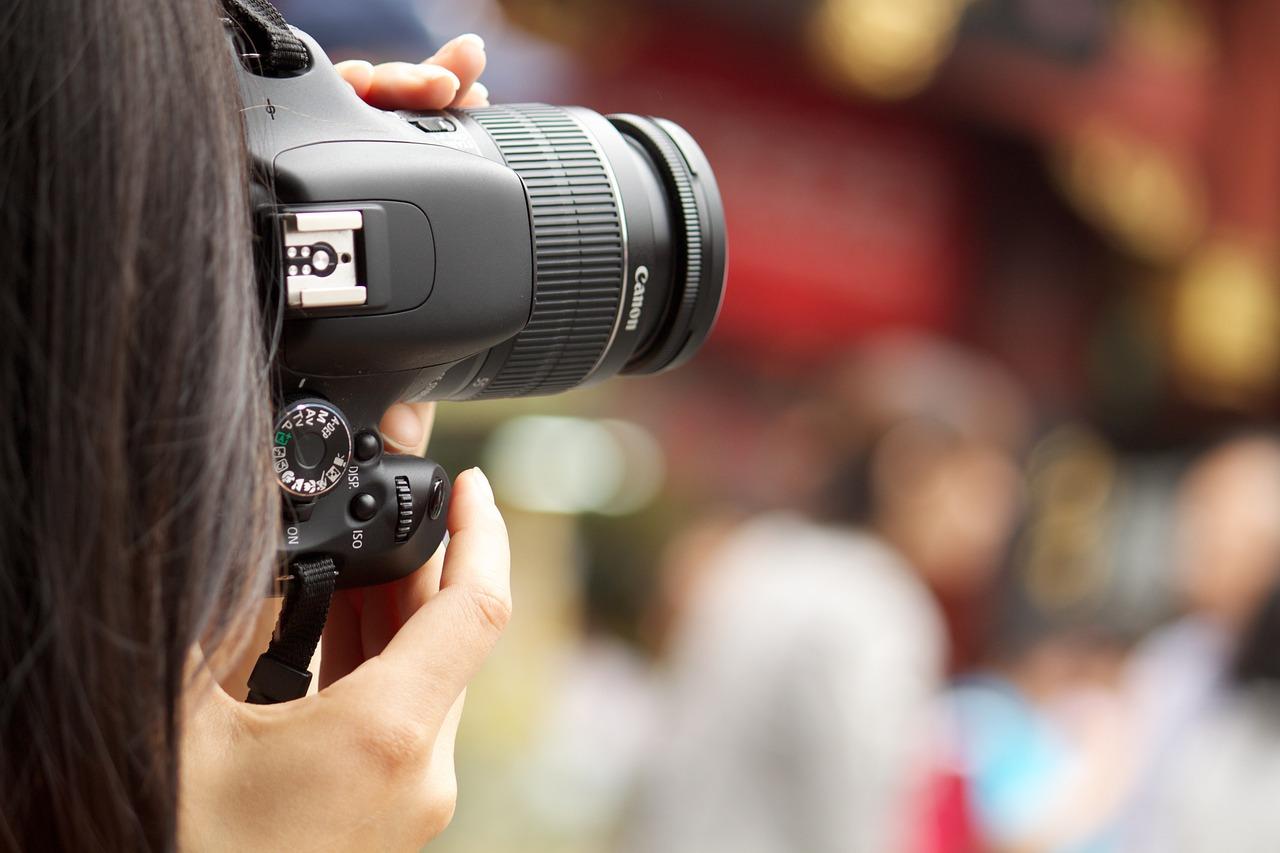 Eine Person guckt durch eine Fotokamera und knipst ein Bild.